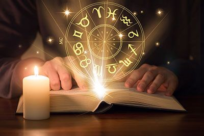 Hands placed on an open book with zodiac signs in a circle and stars  floating above.