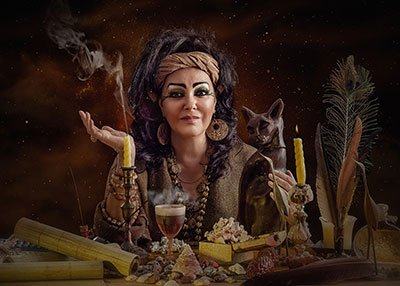 A seated female psychic, in gypsy attire, surrounded by scrolls, incense, candles, feathers and a goblet of wine.