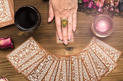 A femle hands drawing a tarot card from a spread of cards, placed face down on a wooden table.